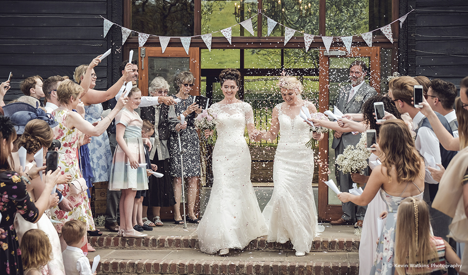 At Upwaltham Barns two brides enjoy a confetti moment outside the East Barn which is adorned with vintage bunting