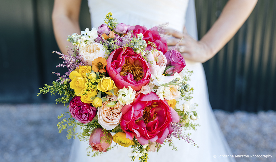 A vibrant pink and yellow wedding bouquet added a perfect pop of colour to this summer wedding at Upwaltham Barns