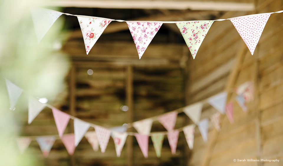 Pretty floral bunting is used to add decoration to a vintage wedding at Upwaltham Barns – wedding ideas