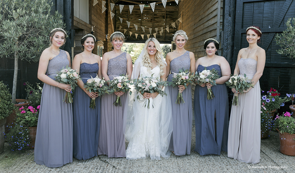 The bride stands alongside her bridesmaids who wear shades of blue and grey