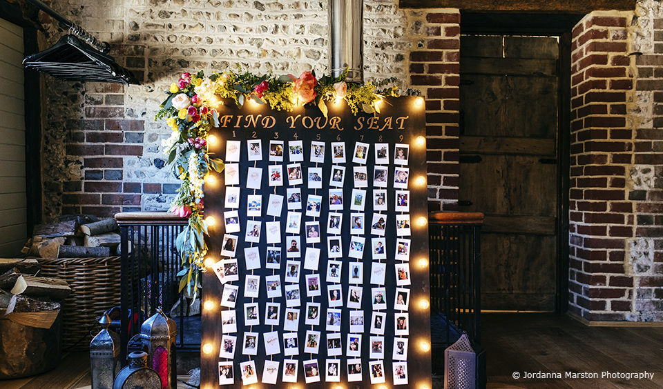 A giant wedding table plan with photos of guests was lit up and adorned with flowers for this summer wedding at Upwaltham Barns