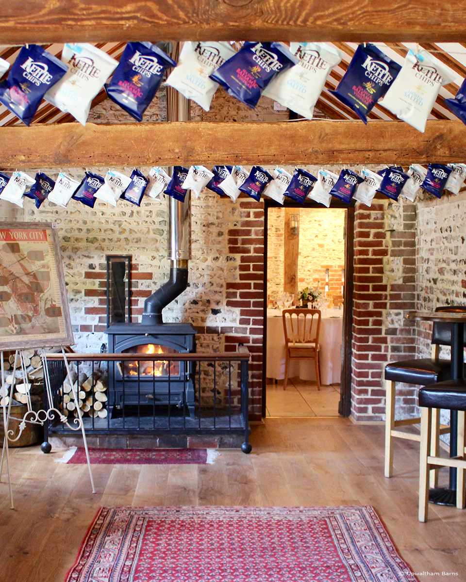 Packets of crisps hang from the beams in the Stable Bar at Upwaltham Barns for a quirky alternative to wedding bunting