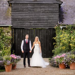 Newlyweds stand outside the East Barn at Upwaltham Barns wedding venue