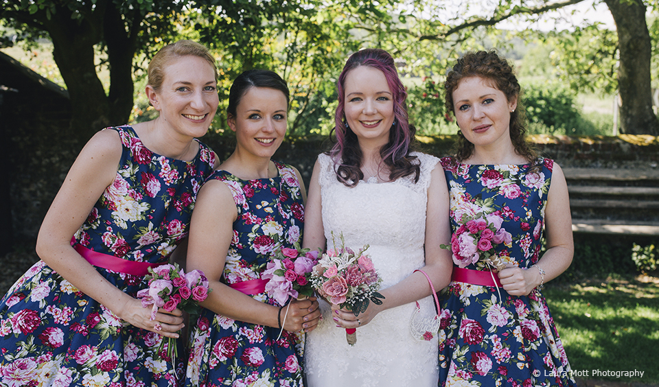 The bride stands with her bridesmaids who wear navy and pink floral bridesmaid dresses