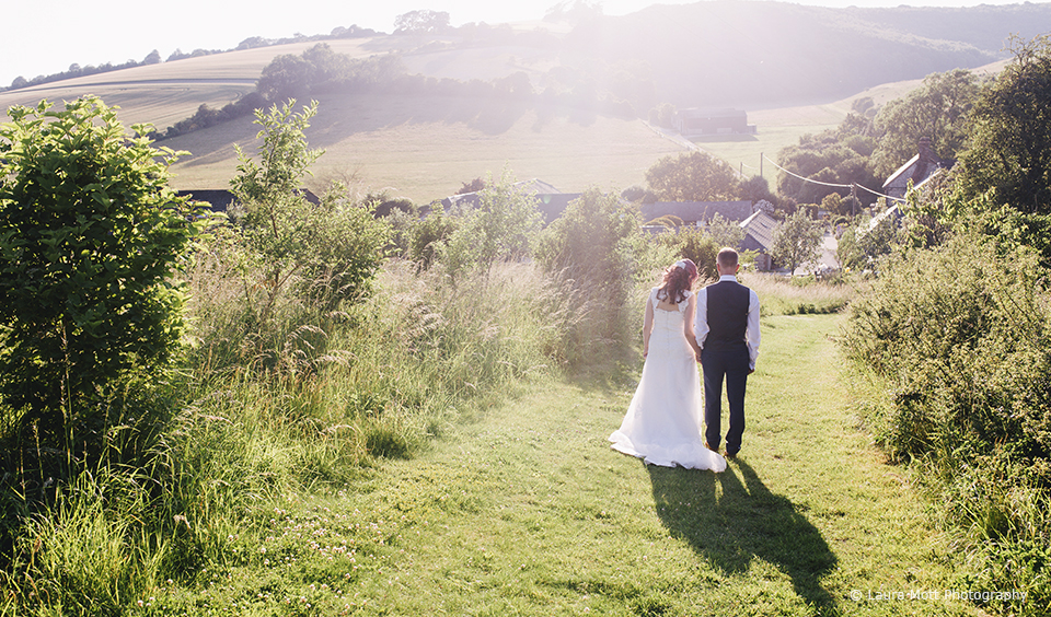 The new husband and wife walk through the countryside that surrounds Upwaltham Barns