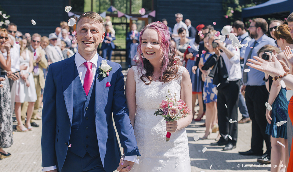 The newlyweds enjoy a confetti moment in the courtyard at Upwaltham Barns in West Sussex