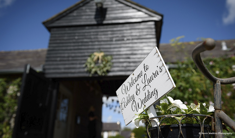 A vintage white wash welcome sign greets wedding guests as they arrive at Upwaltham Barns