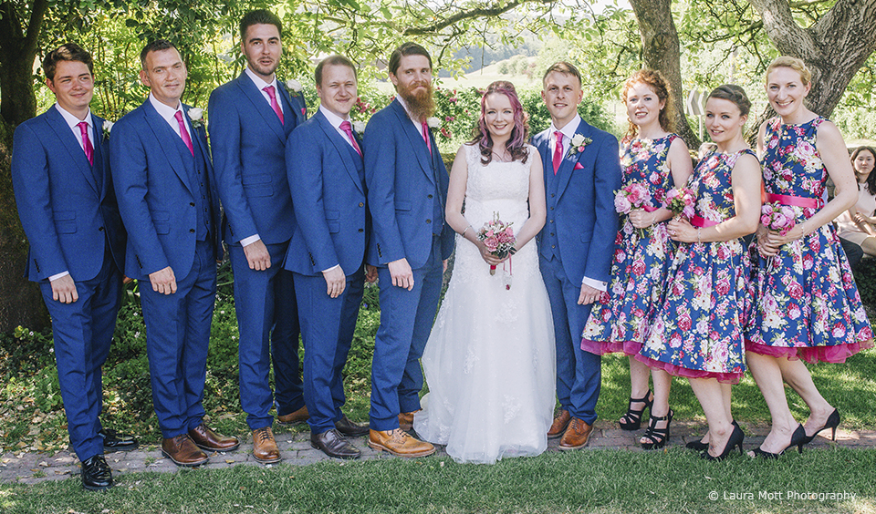 The bridesmaids and groomsmen stand with the bride and groom after the wedding ceremony at Upwaltham Barns