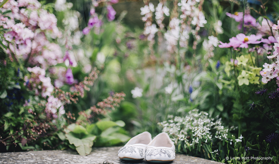 The brides wedding shoes sit in the gardens at Upwaltham Barns in West Sussex