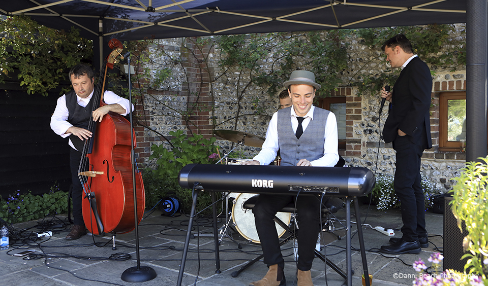 A swing band plays during the drinks reception in the courtyard at the Sussex wedding venue