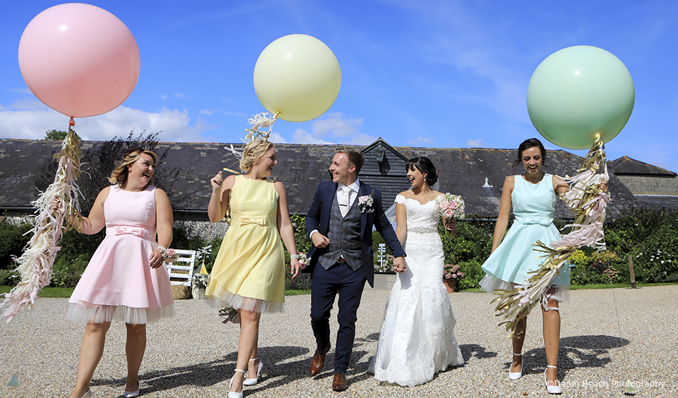 The bridesmaids hold giant balloons alongside the bride and groom in the grounds at Upwaltham Barns