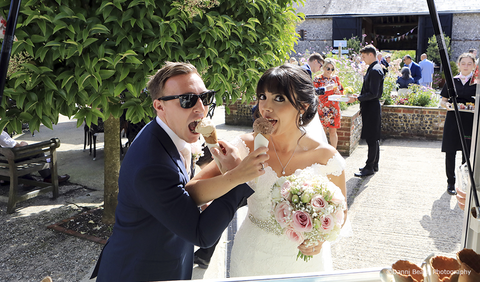 The bride and groom eat ice creams during their wedding reception in the courtyard at Upwaltham Barns