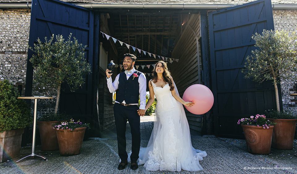 The bride and groom pose for a wedding photo in the courtyard at this Sussex wedding venue