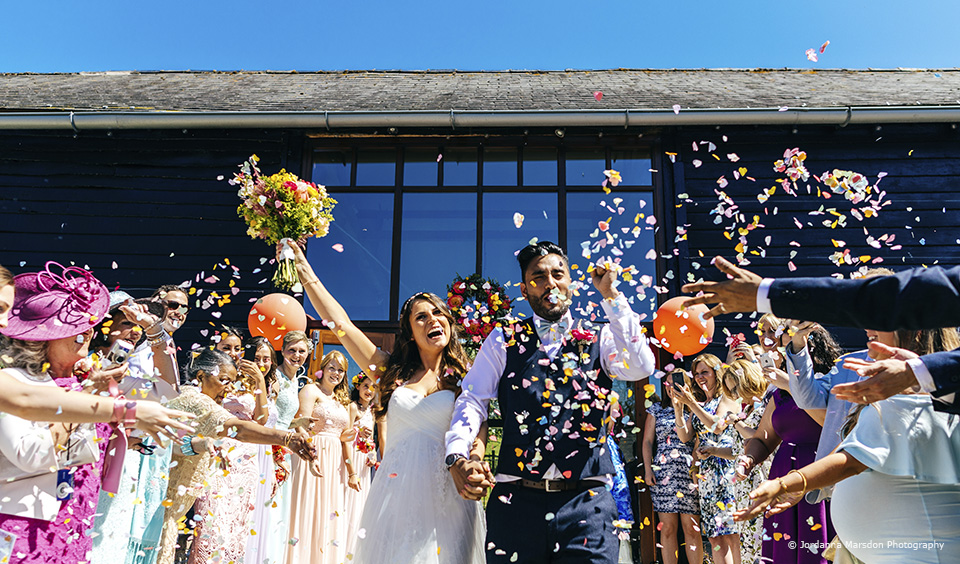 The couple enjoy a confetti moment in the courtyard at Upwaltham Barns in Sussex