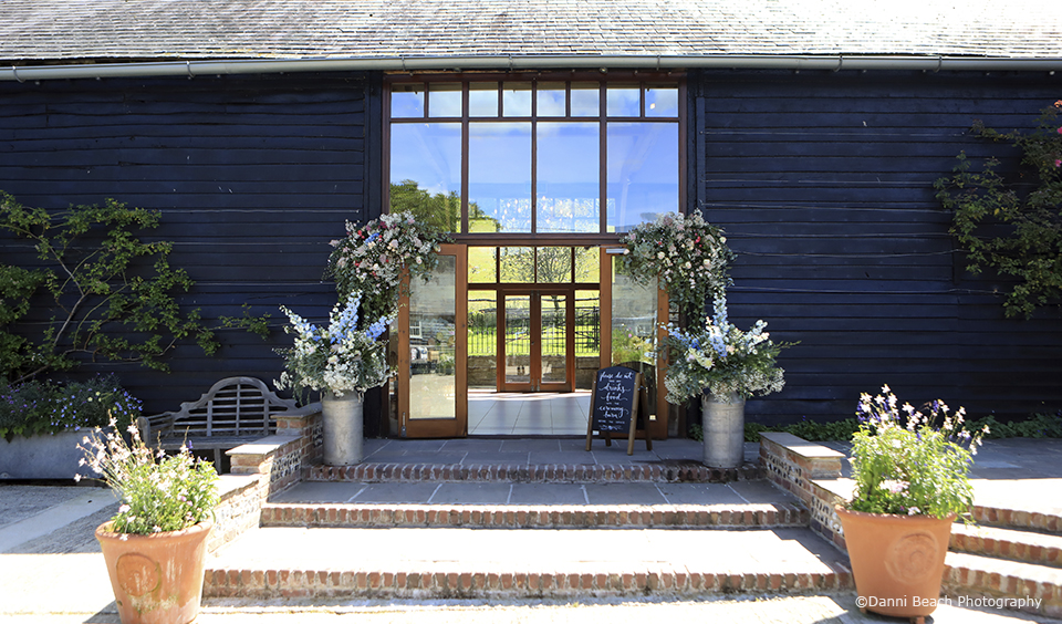 The entrance to the East Barn at Upwaltham Barns is decorated with wedding flowers