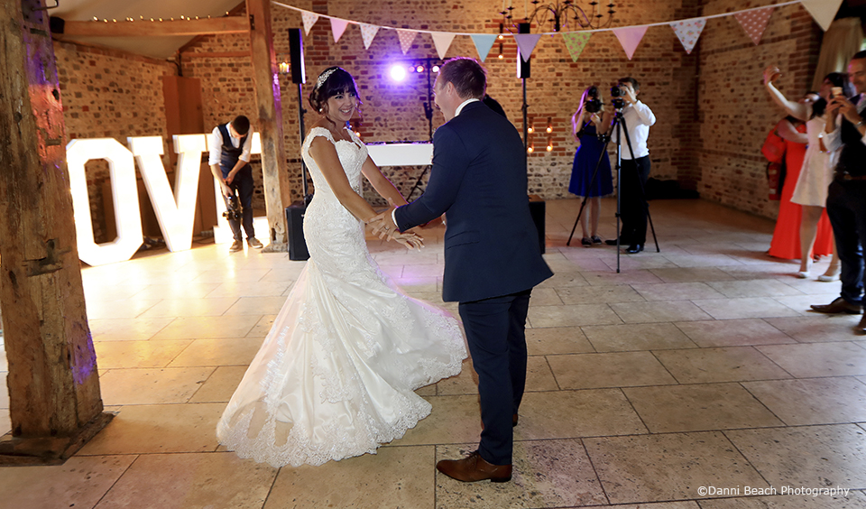 The new husband and wife enjoy their first dance in the South Barn at Upwaltham Barns wedding venue