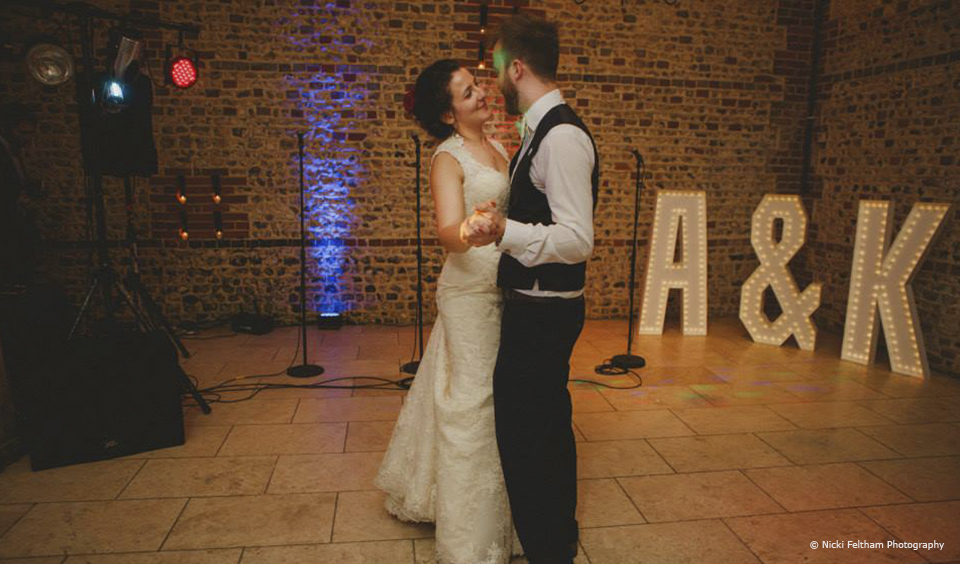 A couple share their first dance in the South Barn at Upwaltham Barns