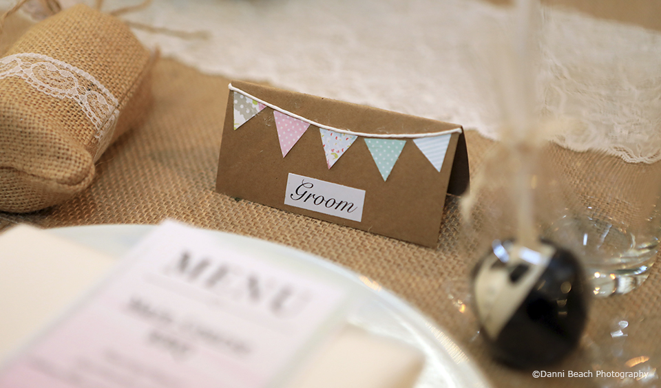 For the wedding reception at Upwaltham Barns name cards are decorated with bunting for a rustic wedding feel
