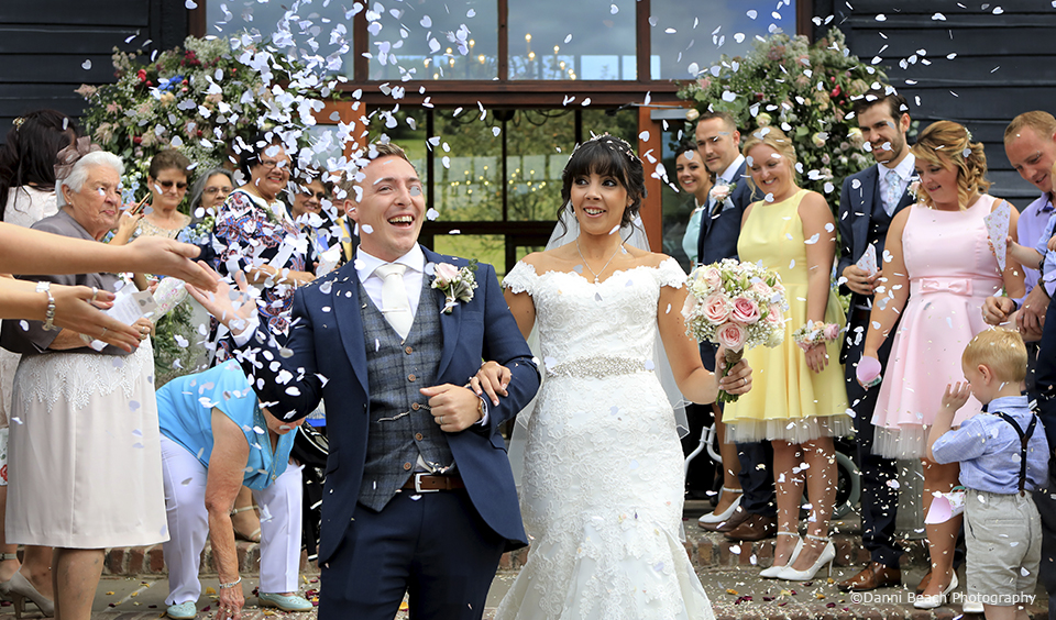 The newlyweds enjoy a confetti moment after their wedding ceremony at Upwaltham Barns