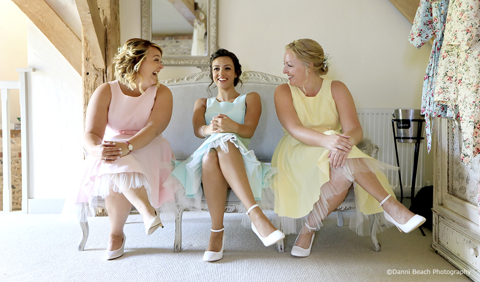 Bridesmaids wear pastel bridesmaid dresses for a rustic wedding at Upwaltham Barns in Sussex