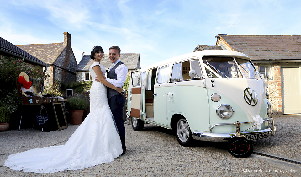 The bride and groom stand next to their VW campervan wedding car at the Sussex wedding venue