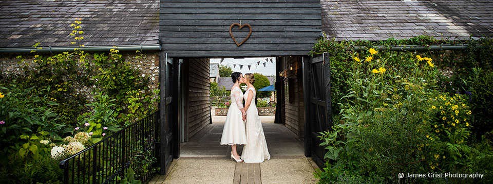 The two brides kissing under the archway at Upwaltham Barns