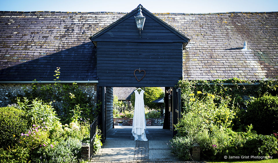 A bridal gown hangs outside Upwaltham Barns wedding venue in Sussex