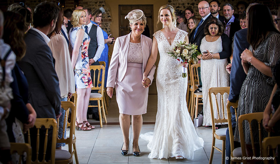 The bride walks down the wedding aisle in the East Barn at Upwaltham Barns in Sussex