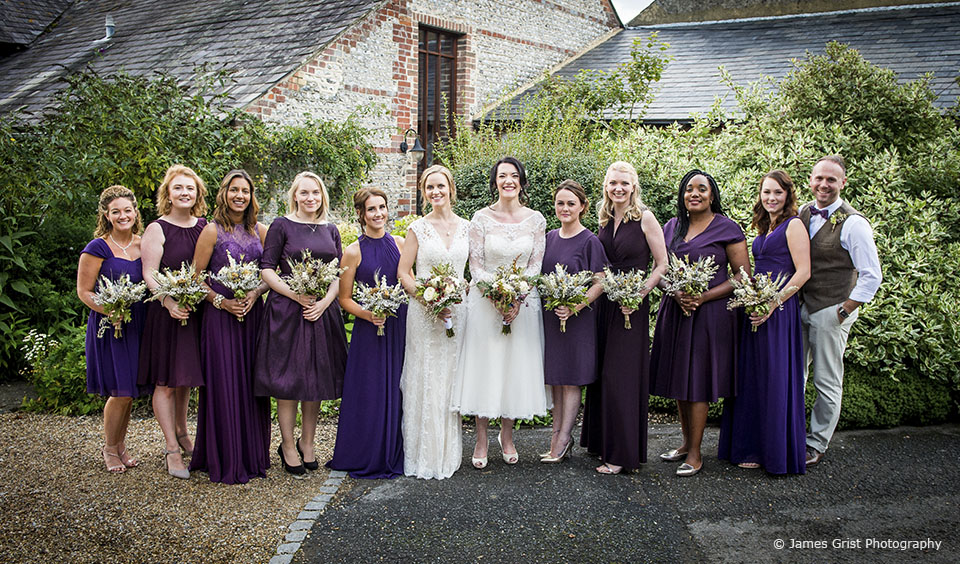 The brides are joined by the bridal party after their wedding ceremony at Upwaltham Barns