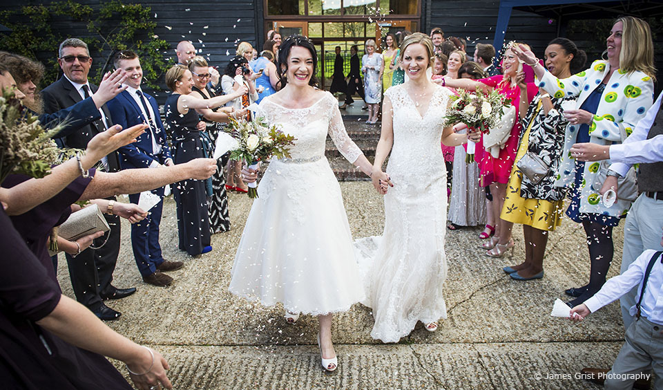The brides enjoy a confetti moment after their wedding ceremony at Upwaltham Barns wedding venue