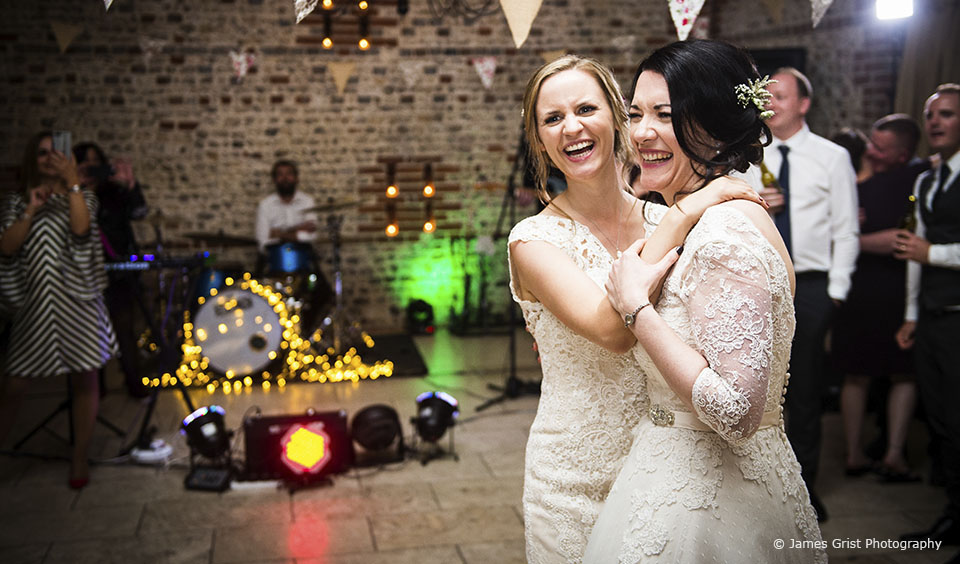 Brides enjoy their first dance in the South Barn at Upwaltham Barns wedding venue in Sussex