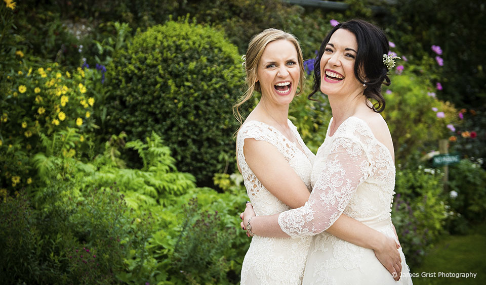The brides enjoy the gardens during their wedding day at Upwaltham Barns in Sussex