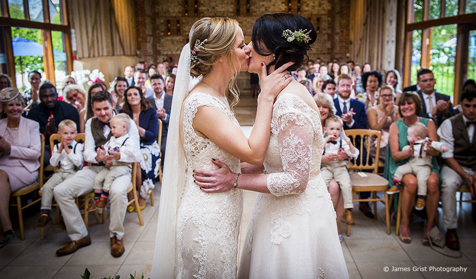 The brides say I do during their wedding ceremony at Upwaltham Barns wedding venue in Sussex