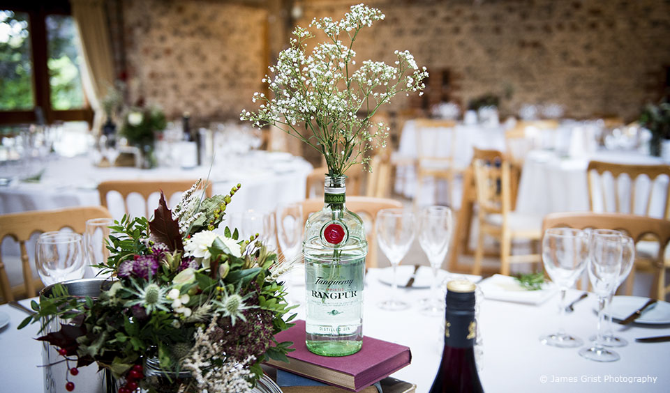 Gin bottles were used as wedding table centrepieces for the wedding reception at Upwaltham Barns in Sussex