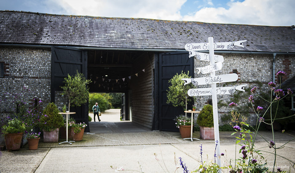 A sign outside the East Barn directs wedding guests around Upwaltham Barns wedding venue in Sussex