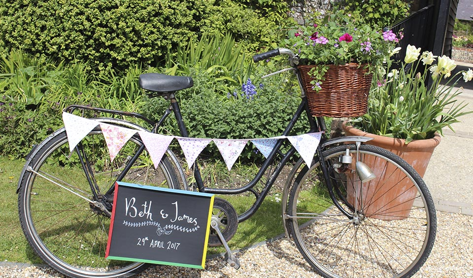 Use a bike as a vintage prop to welcome guests to your wedding at Upwaltham Barns