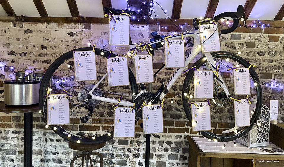 Mount your favourite bike in the wedding barn at Upwaltham Barns and attach seating cards for a fun table plan idea