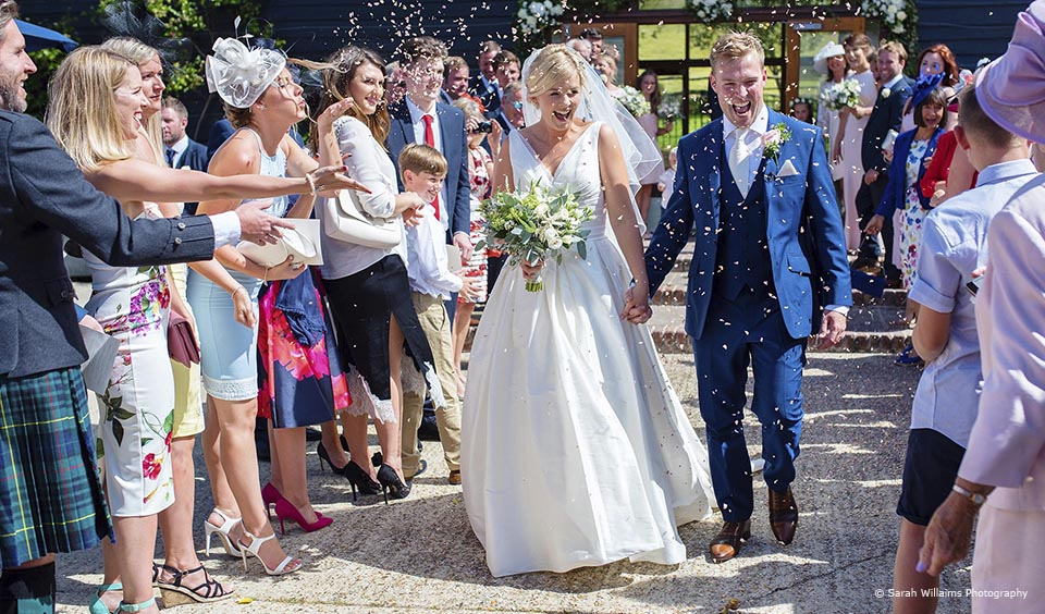 A bride and groom enjoy a confetti moment after their wedding ceremony at Upwaltham Barns