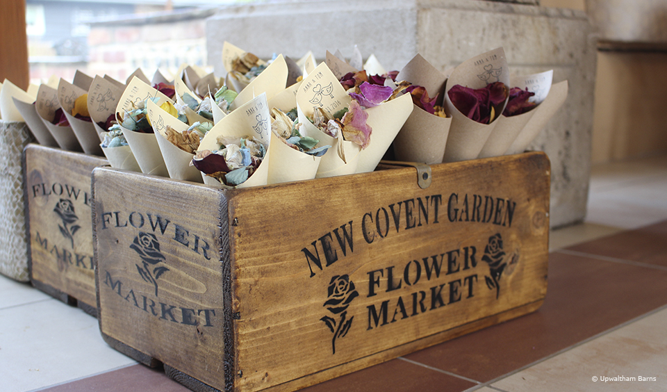 Confetti cones sit in a wooden crate for guests to collect after the wedding ceremony at Upwaltham Barns