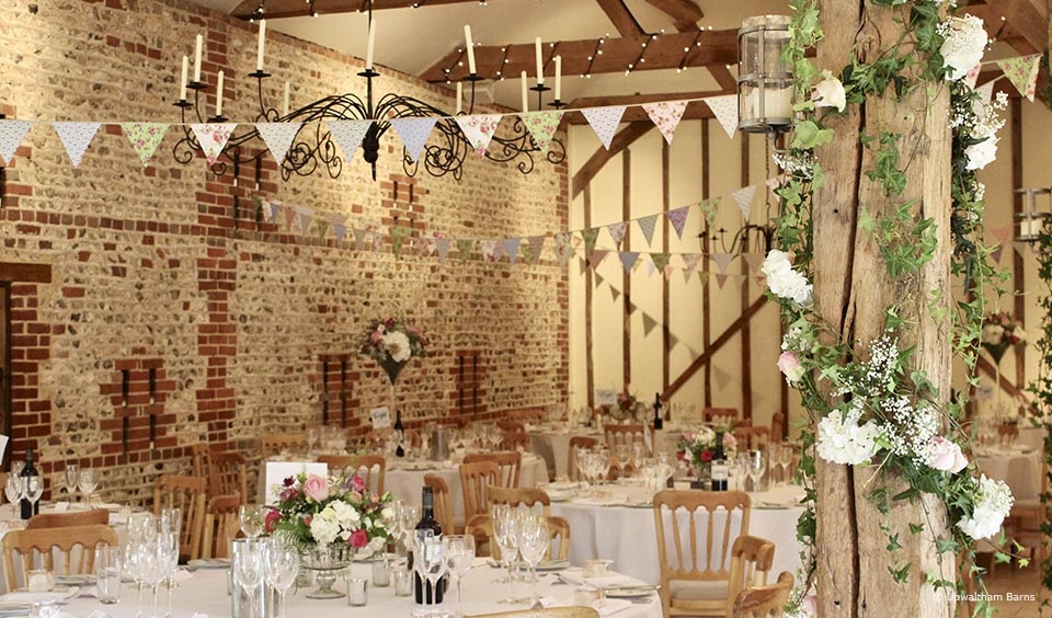 The South Barn at Upwaltham Barns is decorated with bunting and florals for a traditional country wedding