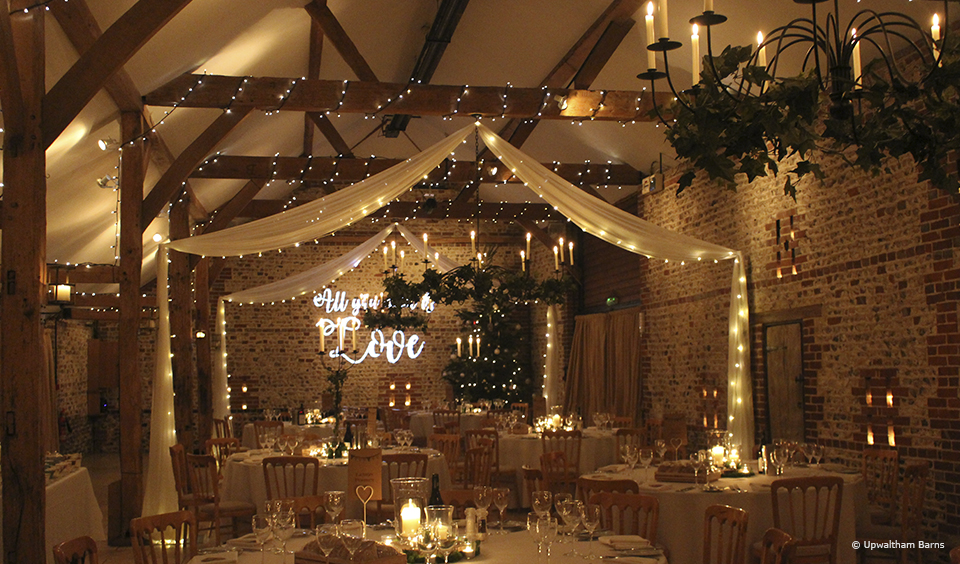 Swags of fabric adorned with fairylights hang from the South Barn at Upwaltham Barns