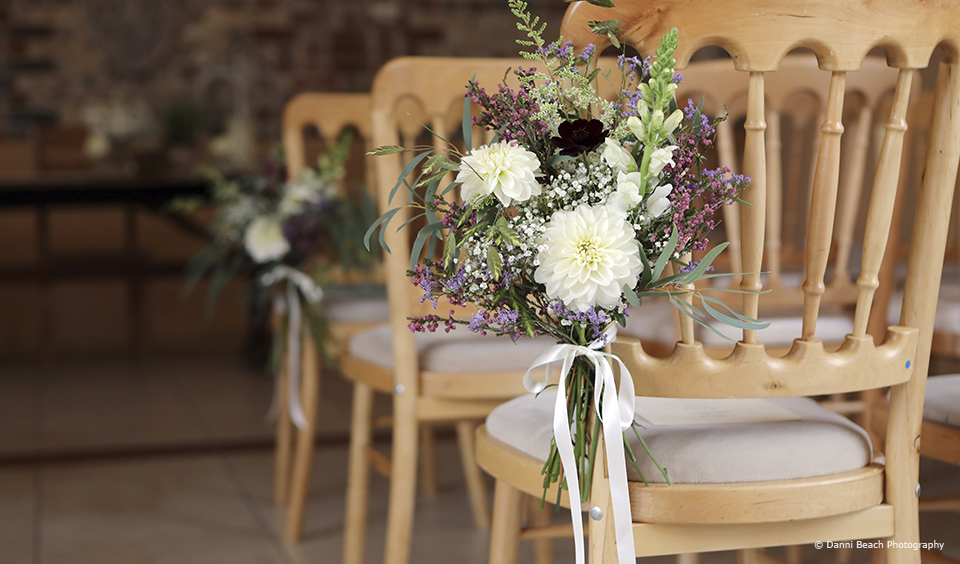 Floral posies are attached to chairs lining the aisle in the East Barn at Upwaltham Barns