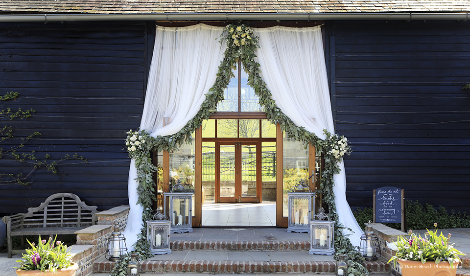 A white curtain edged with green foliage hangs from the doors to the East Barn with lanterns lining the path