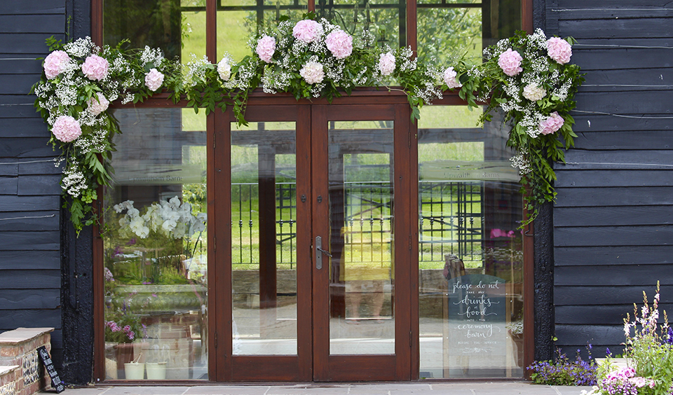 A pink and greenery filled flower garland hangs above the East Barn at Upwaltham Barns