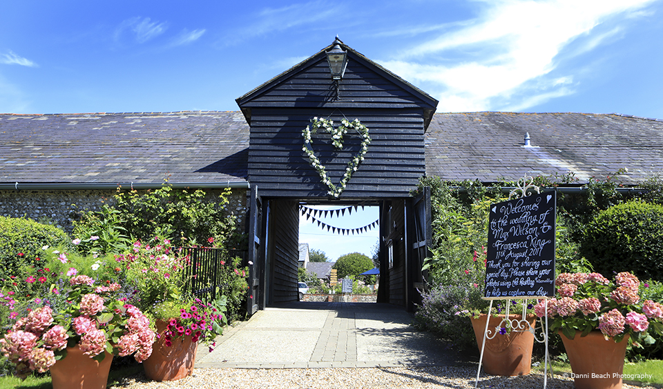 A floral heart hangs above the entrance to Upwaltham Barns – wedding idea