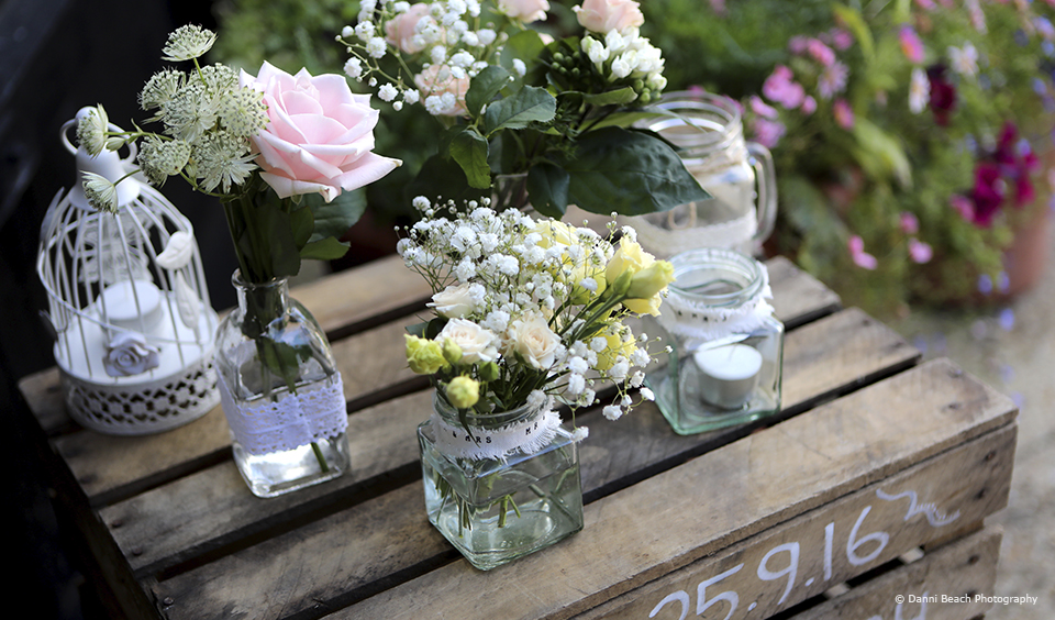 Jam jars are filled with flowers and sit on top of an apple crate for a simple wedding decoration at Upwaltham Barns