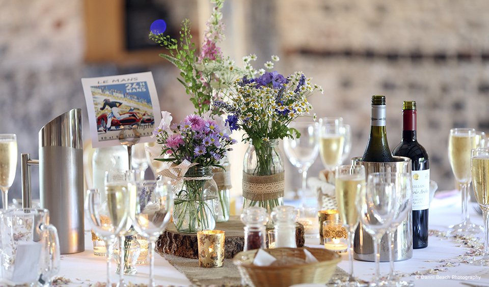 Jam jars filled with flowers decorate the tables in the South Barn at Upwaltham Barns