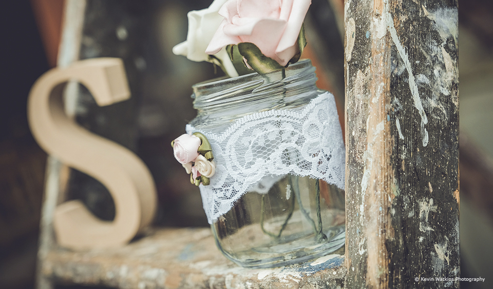 Lace is wrapped around jars for a simple wedding decoration at Upwaltham Barns