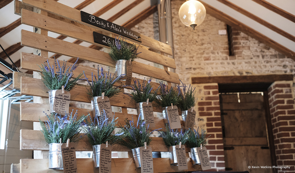 Use wooden pallets as your table plan at Upwaltham Barns for a rustic wedding theme