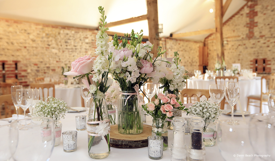 Pink flowers are placed in glass vases and jars for a traditional look at Upwaltham Barns